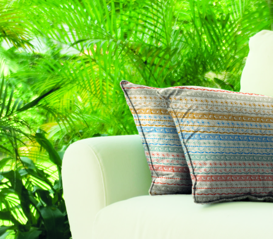 White Sofa With Green Pillows On It Placed Outdoors